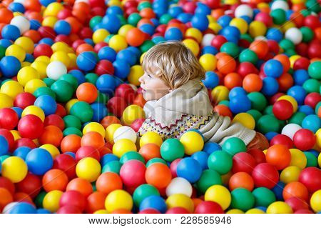 Happy Laughing Kid Boy Having Fun In Ball Pit On Birthday Party In Kids Amusement Park And Indoor Pl