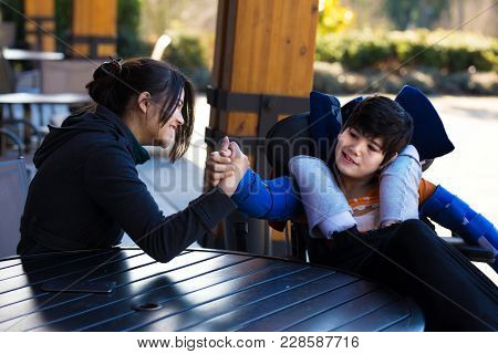 Handsome Biracial Asian Caucasian Disabled Boy In Wheelchair Playing Arm Wrestling With Sister Or Ca