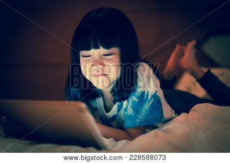 Asian Kid Girl Enjoy Using Online Internet For Social Communicate With Friends While Lying On The Be