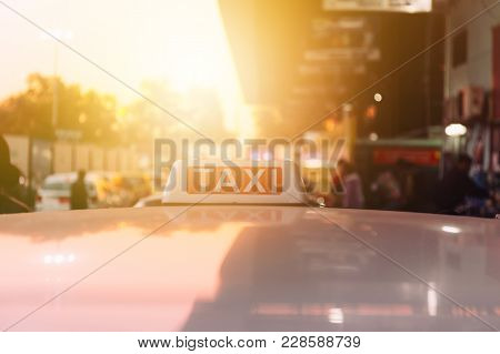 Taxi Sign On The Roof Of Taxi Cab On The Busy Street Over Yellow Orange Warming Sunset Background