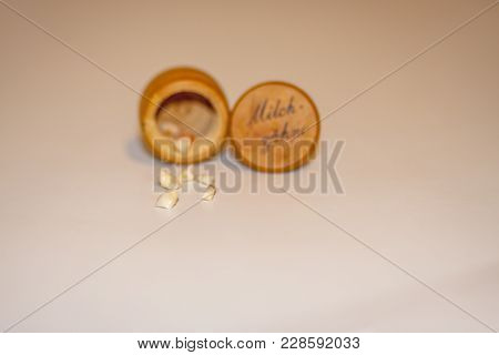 Collection Of Extracted Milk Teeth In Front Of Wooden Box - Translation: Milk Teeth.
