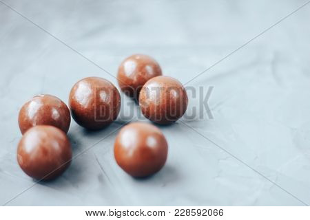 Round Chocolate Bon-bons. Sweets Chocolate Dragees On Grey Background