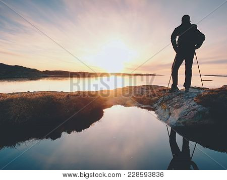 Young Standing Man With Backpack. Hiker On The Stone On The Seashore At Colorful Sunset Sky. Beautif