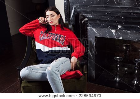 Trendy Young Woman Ia Red Hoodies. Portrait In Fashionable Interior.
