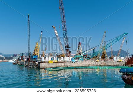 Hong Kong January 29, 2016: Construction Site On The Water And Work Of Construction Cranes Next To T