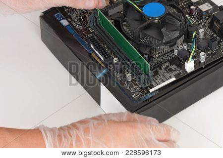 Close Up Of Man Hands With Gloves Installing Ram Ddr4 Memory Module In Slot On Motherboard.