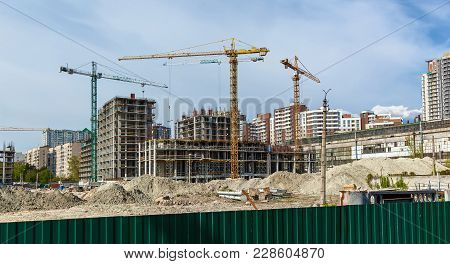 Site Buildings Under Construction And Cranes. High-rise Building Under Construction. The Site With C