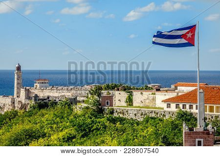 El Morro Spanish Fortress With Lighthouse, Cannons And Cuban Flag In Th Foreground, With Sea In The