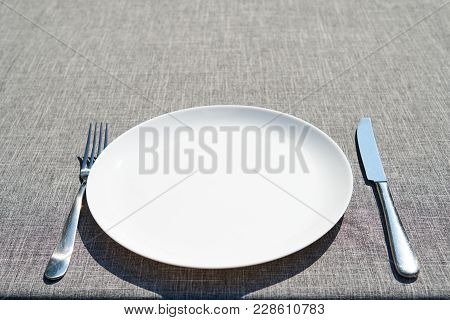Empty Ceramic Round Plate And Cutlery On Grey Tablecloth, Copy Space. Dinner Plate Setting. White Pl