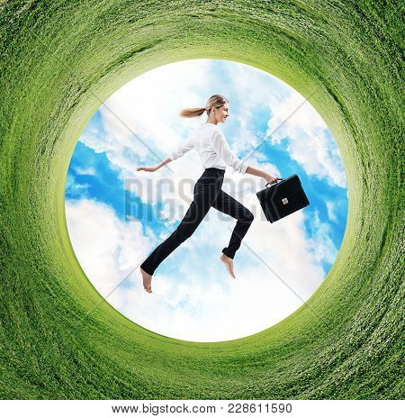 Business Woman Jumps In Formal Wear In Rotated Field With Green Grass.