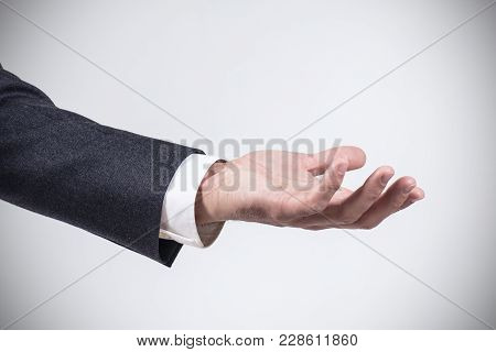Man In Business Suit Standing And Shows Outstretched Hand With Open Palm.