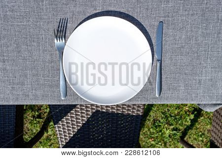 Empty Ceramic Round Plate And Cutlery On Grey Tablecloth Outdoors, Copy Space. Dinner Plate Setting.