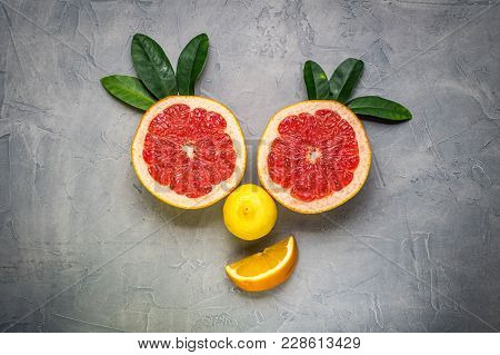 Creative Collage: A Smiling Face Made Of Grapefruit And Lemon On A Gray Background
