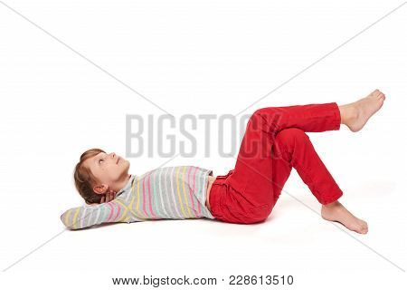 A Child Girl Lying On Her Back On The Floor With Crossed Legs Looking Up At Blank Copy Space, Over W