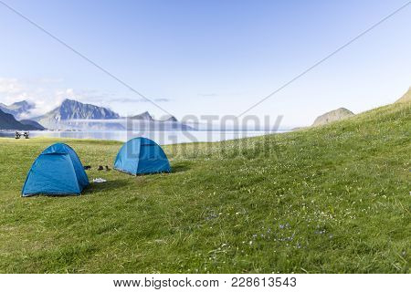 Two Tents In The Green Grass In Front Of The Sea. Haukland Beach, Lofoten Islands, Norway.