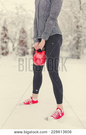 Woman Holding Red Kettlebell In Snow Concept, Outdoor Workout, Endurance