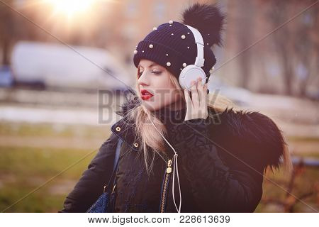 Young Blonde Woman In Winter Cap With Red Lips Listening Music Outdoor, Singing