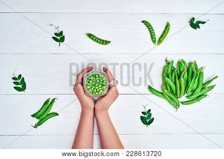 Woman Holding In Hands Glass Jar With Fresh Green Peas On White Wooden Background, Copy Space. Bio H