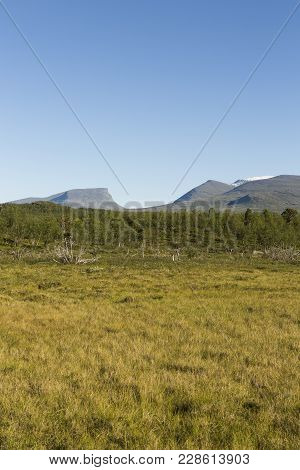Lapporten, A Mountain Pass In Lapland, Sweden Viewed From Far Away. Sky Is Clear Blue And Grass In T