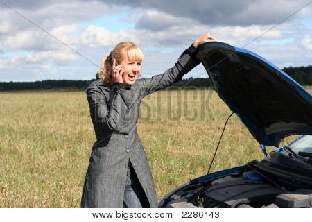 Young Blond Woman With Her Broken Car. The Girl Is Angry