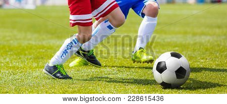 Football Player Running And Kicking Ball On Grass Pitch. Soccer Striker And Defender Competition