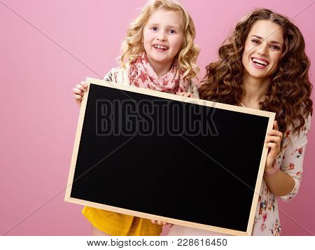 Mother And Daughter On Pink Background Showing Blank Board