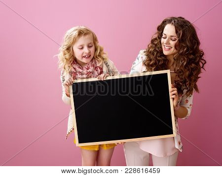 Pink Mood. Smiling Stylish Mother And Child With Wavy Hair On Pink Background Looking At Black Board