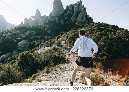 Professional Runner Athlete Runs Away From Camera, During Ultra Marathon Training Or Jogging Through