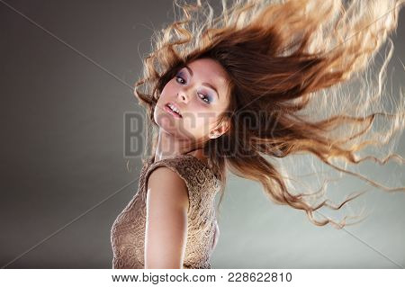 Mysterious Enigmatic Woman In Studio On Grey. Young Intriguing Attractive Girl With Flying Long Curl