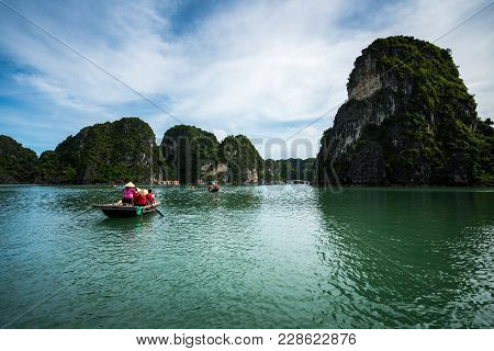 Halong Bay In Vietnam, Unesco World Heritage Site, With Tourist Rowing Boats