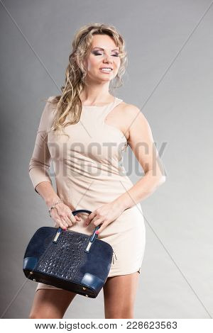 Fashion Of Women. Clothing And Accessories. Mid Aged Blonde Fashionable Woman With Deep Blue Handbag