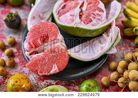 Appetizing Exotic Fruit On The Shabby Wooden Red Table. There Is A Sliced Pomelo On The Black Plate,