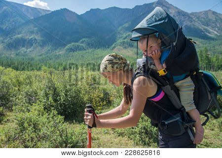 Tired Woman Hiker Trekking In Mountains With Child In Backpack, Stopped For Rest. Mother With Baby B