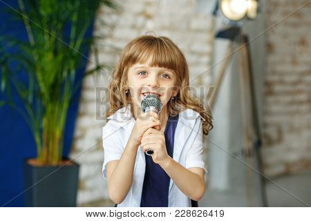 A Little Beautiful Girl Sings In A Microphone. The Concept Is Childhood, Lifestyle, Music, Singing,