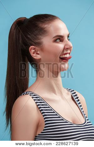 Beautiful Female Three-quarters Portrait. Isolated On Blue Studio Backgroud. The Young Emotional Cra