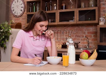 Eat Healthy Feel Wealthy. Beautiful Smiling Young Lady Sitting In The Kitchen And Writing Her Diary
