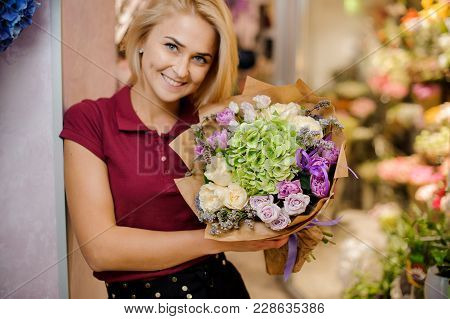 Girl Holding A Bouquet Of Roses, Callas, Orchid And Hydrangea In Golden Wrapping Paper With A Pink R