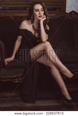 An Attractive Young Woman In A Long Black Dress With A Deep Neckline, With Long Legs Sitting On The