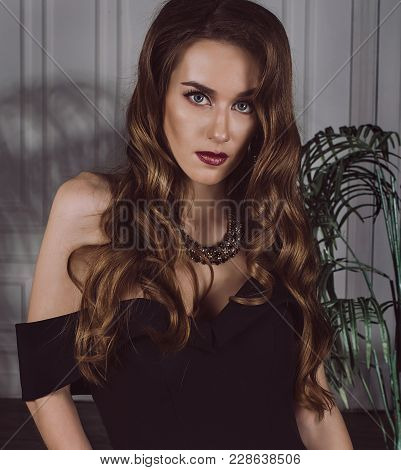 Portrait Of An Attractive Stylish, Sexy Brown-haired Woman In A Black Dress With Open Shoulders In T