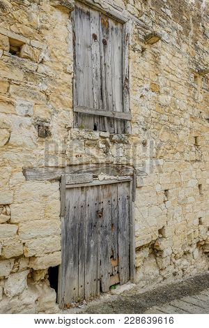 Dilapidated Closed Wooden Doors In An Ancient Stone Wall.