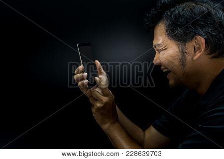 Asian Man Smiling Using Smartphone In Dark Style