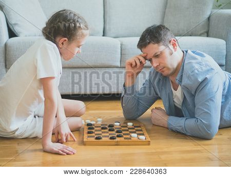 Father And Daughter Playing Checkers Board Game.