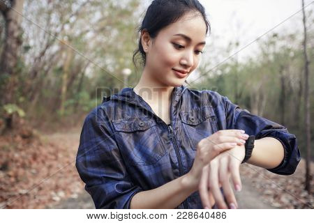 Female Runner Checking Smart Watch Fitness Tracker And Smiling After Jogging And Runners Legs