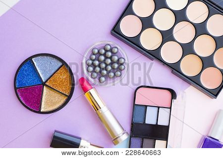A Set Of Professional Concealer And Eyeshadow Palettes, Pink Lipstick And Colorful Glitter On A Past