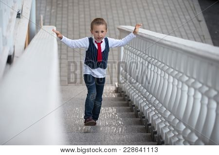 A Child In A Tie Climbs Up The Stairs