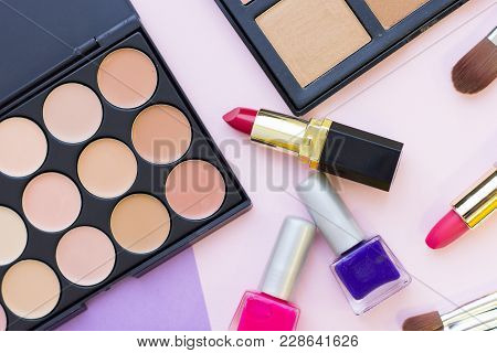 A Close Up Of Face Foundation, Concealer, Palettes, Lipstick And Nail Polish On A Pastel Pink Backgr