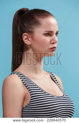 Beautiful Female Three-quarters Portrait. Isolated On Blue Studio Backgroud. The Young Emotional Ang