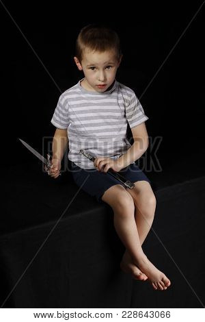 Little Boy With A Dagger On A Black Background