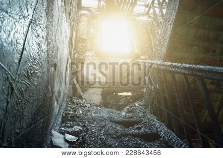 Interior Of Burnt By Fire Building. Burned Wooden Staircase In Sun Light, Toned