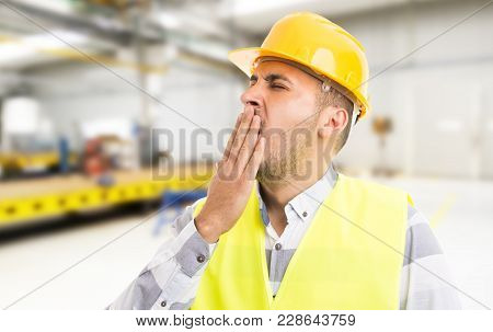 Tired Workman Yawning Sleepy On Workplace Inside Factory.